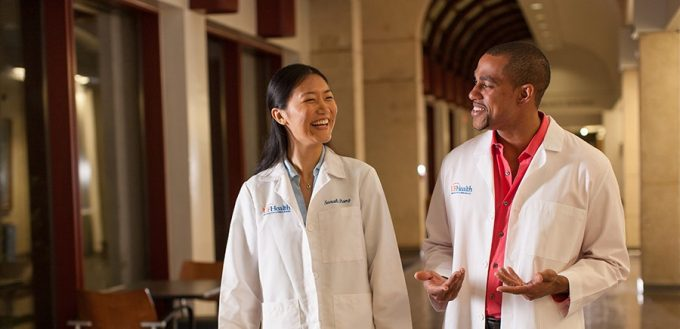 Two students wearing white coats talking while walking through the Founders Gallery