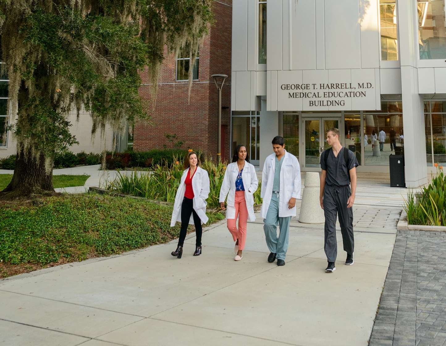 Four Medical Students walking in front of The Harrell Medical Education building