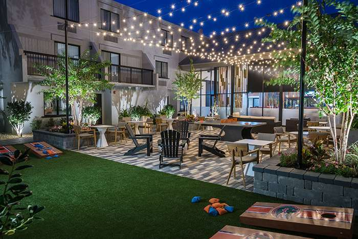 DoubleTree hotel courtyard with string lights and games