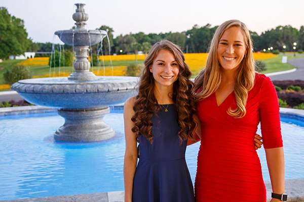 Two students pose for a photo outside by a fountain.