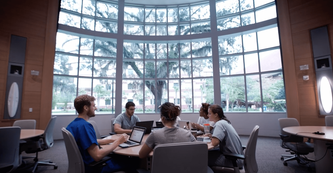 A group of students sitting in the learning studio of the Harrell Medical Education Building.